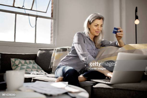 mature woman holding debit card while using laptop on sofa - home shopping stock pictures, royalty-free photos & images