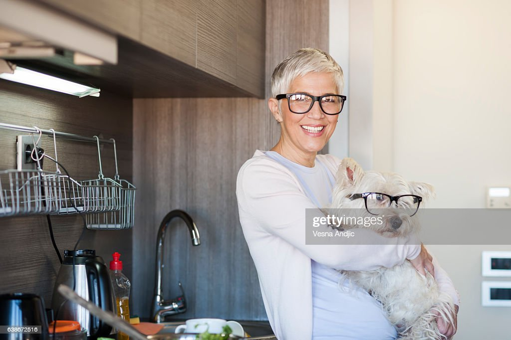 Mature woman holding dog at home : Stock Photo