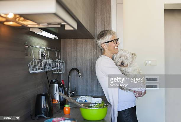 Mature woman holding dog at home