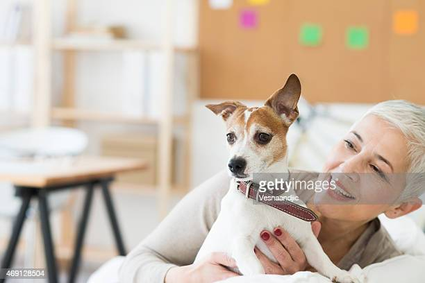 Mature woman holding dog while smiling