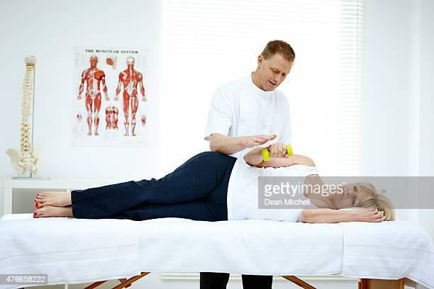Mujer madura con physiotherapist pesa ejercicio de retención