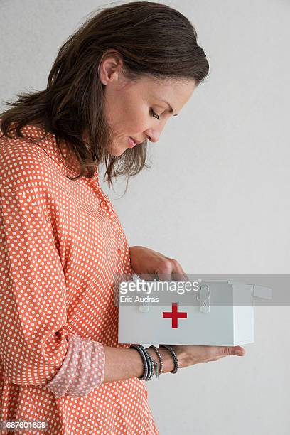 Mature woman holding first aid kit