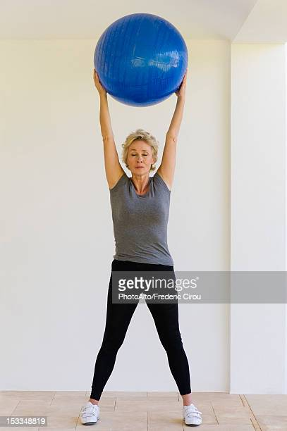 Mature woman holding fitness ball overhead with eyes closed
