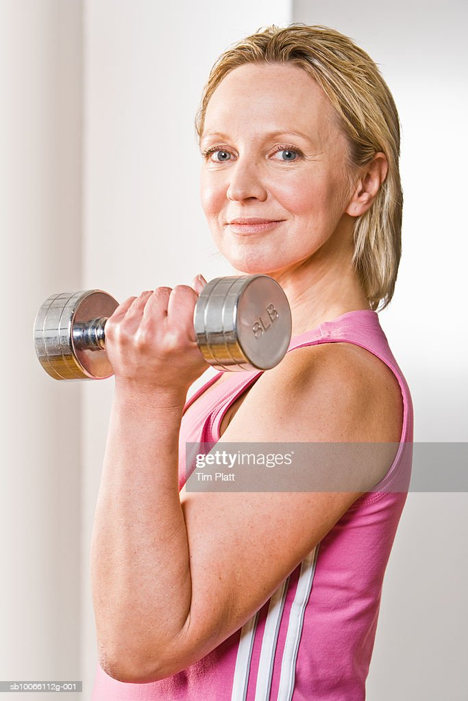 Mature woman holding free weight, smiling, close-up, portrait : Stock Photo