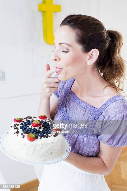 Mature woman holding fruit covered cake, licking fingers eyes closed