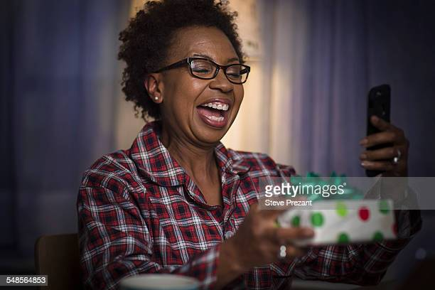 Mature woman holding gift taking selfie at home