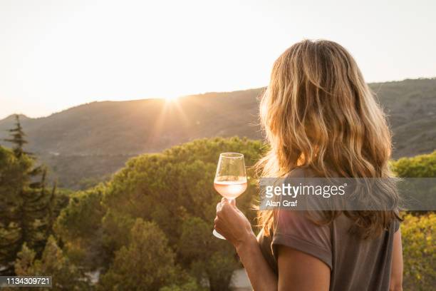 mature woman holding glass of wine watching sunset over hills, rear view, portoferraio, tuscany, italy - wine stock pictures, royalty-free photos & images