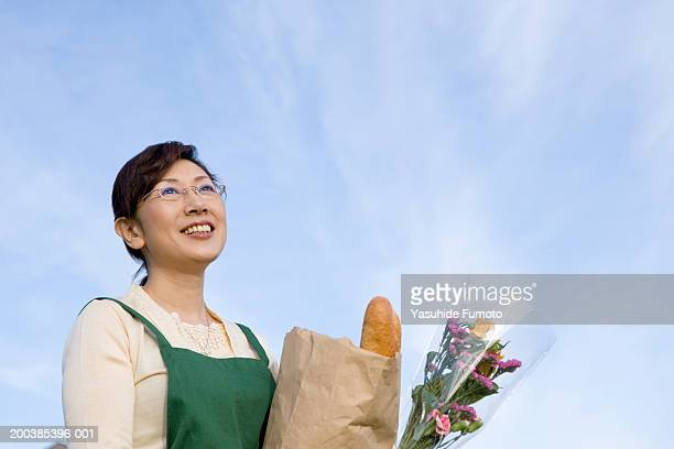 Mature woman holding grocery bag outdoors, smiling, low angle view