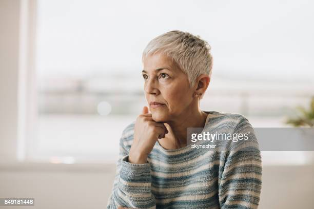 Mature woman holding hand on chin and thinking about something.
