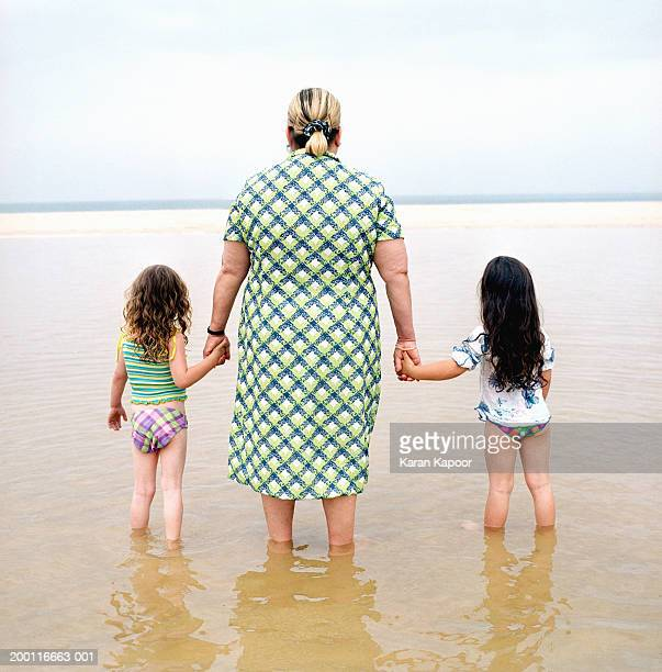 Mature woman holding hands with two girls (3-5) on beach, rear view