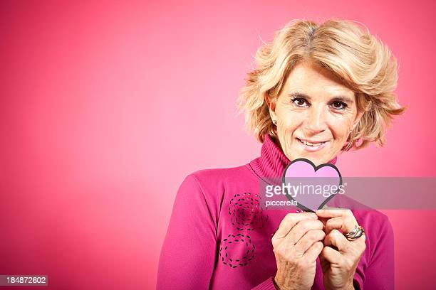 mature woman holding heart - menopause stock photos and pictures