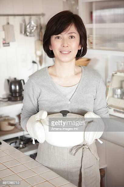 Mature woman holding hot pot