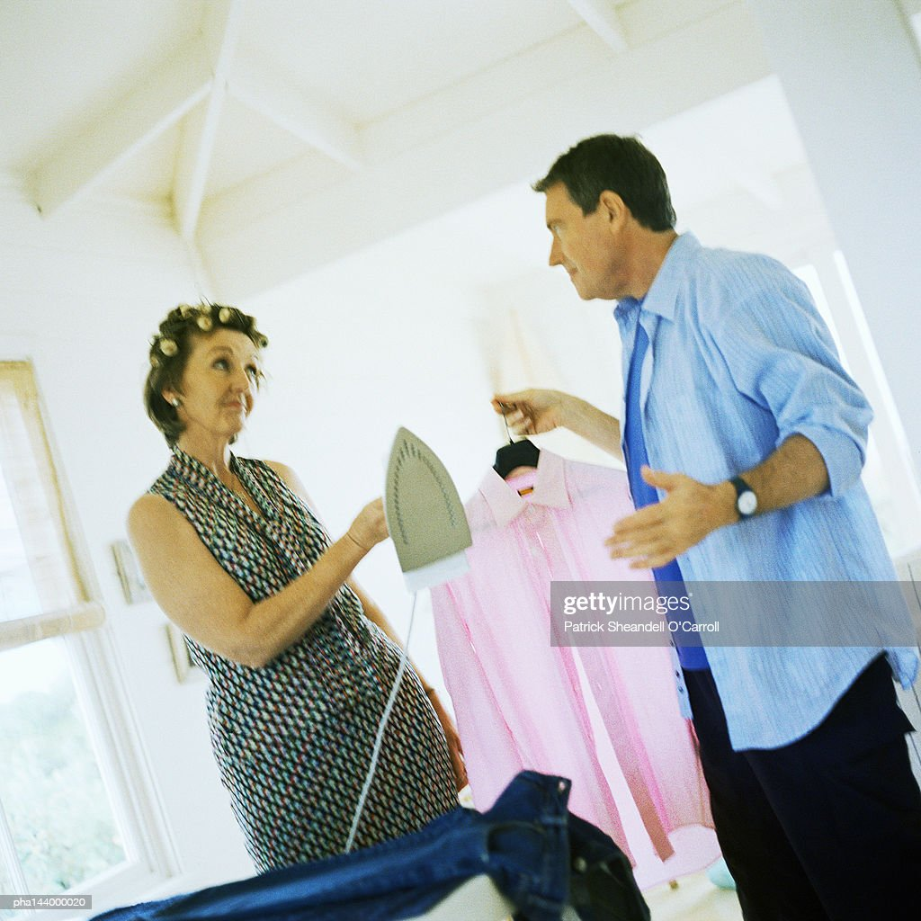Mature woman holding iron, man holding shirt : Stockfoto