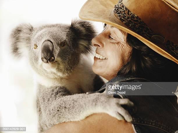 Mature woman holding koala, close-up