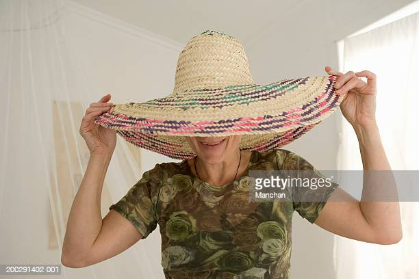 Mature woman holding large hat on head, smiling
