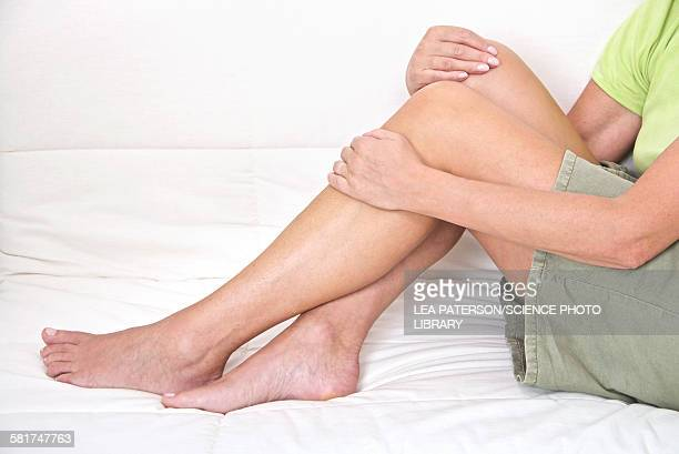mature woman holding legs - older woman legs stock photos and pictures