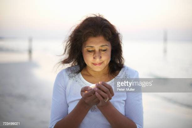 Mature woman holding light on beach at dusk, Dubai, United Arab Emirates