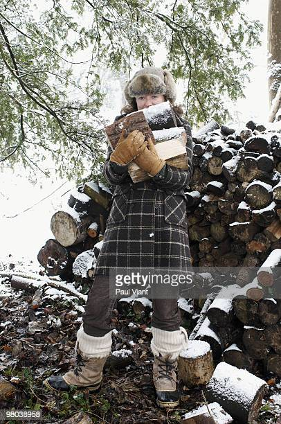 mature woman holding logs in snow