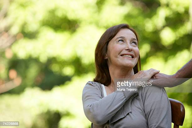 """mature woman holding man's hand, looking away"" - hand on shoulder stock pictures, royalty-free photos & images"