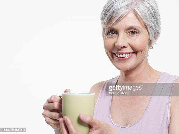 Mature woman holding mug, smiling, portrait, close-up