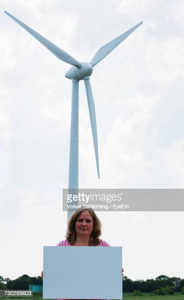 Mature Woman Holding Placard While Standing Against Windmill