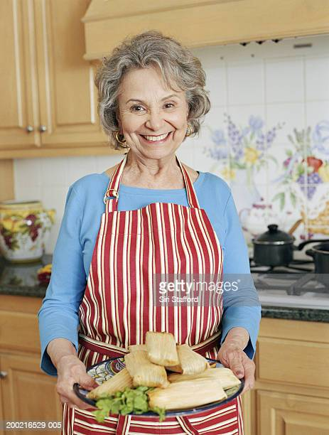 Mature woman holding platter of tamales