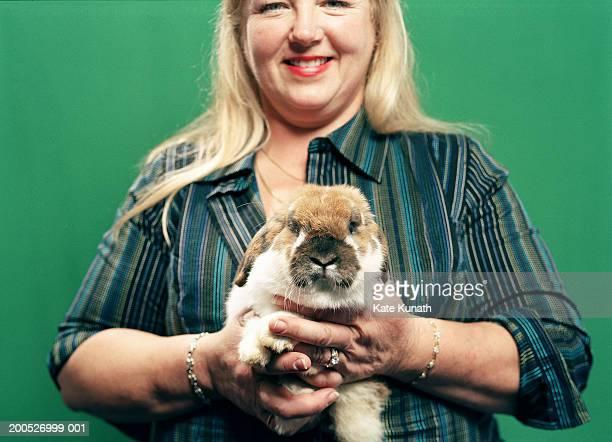 Mature woman holding rabbit, smiling, close-up, portrait