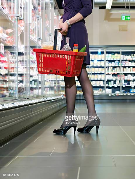 mature woman holding shopping basket - hoge hakken stockfoto's en -beelden