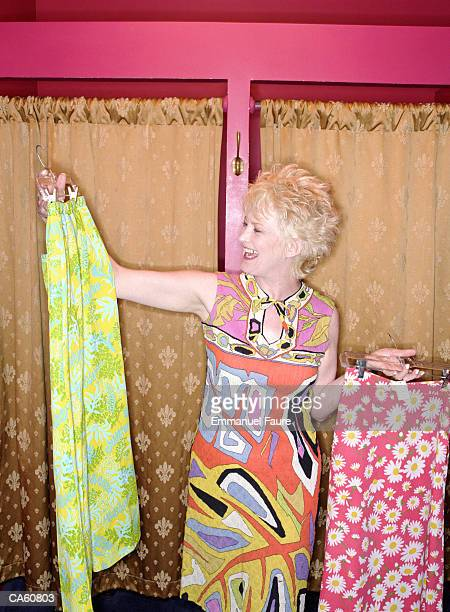 mature woman holding skirts up in shop - older women in short skirts stock pictures, royalty-free photos & images