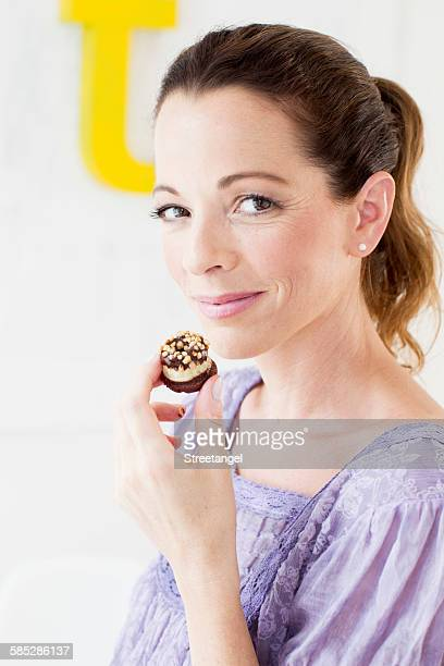 Mature woman holding sweet baked product looking at camera smiling