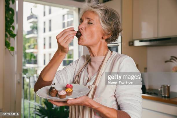 Mature woman holding tasting something from her self-made mini desserts