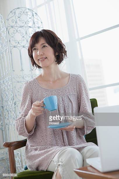 Mature woman holding tea cup, looking away