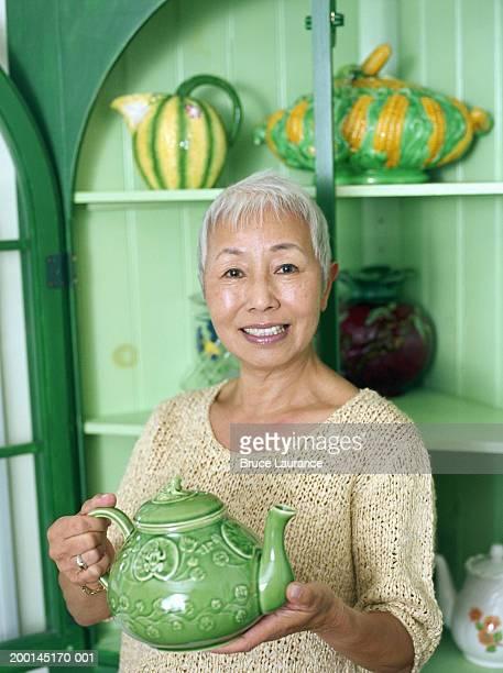 Mature woman holding teapot, portrait