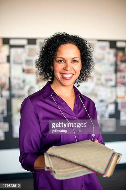 mature woman holding textile swatch - purple shirt stock photos and pictures