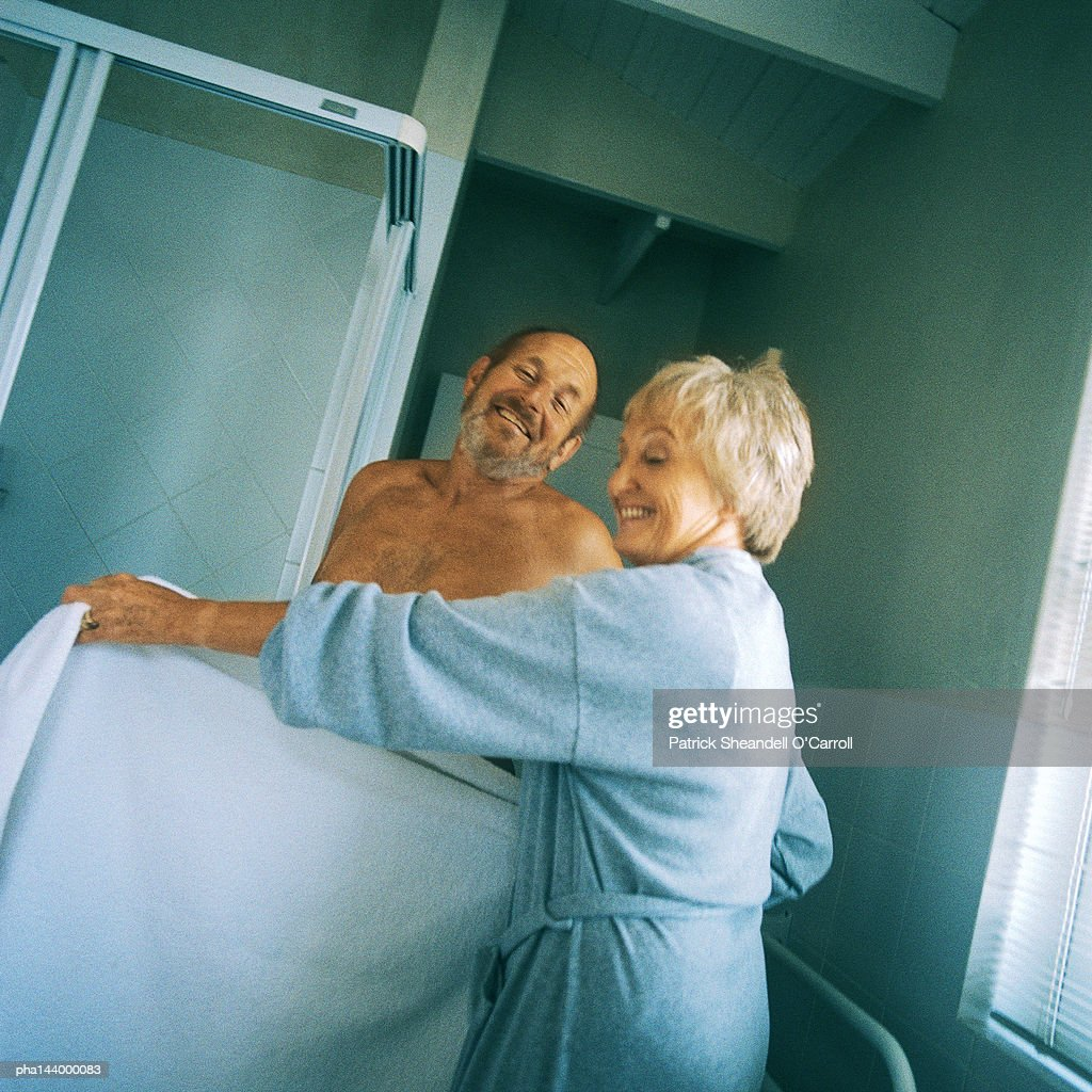 Mature woman holding towel in front of nude man : Stockfoto