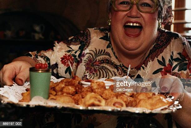 Mature woman holding tray of hors d'oeuvre