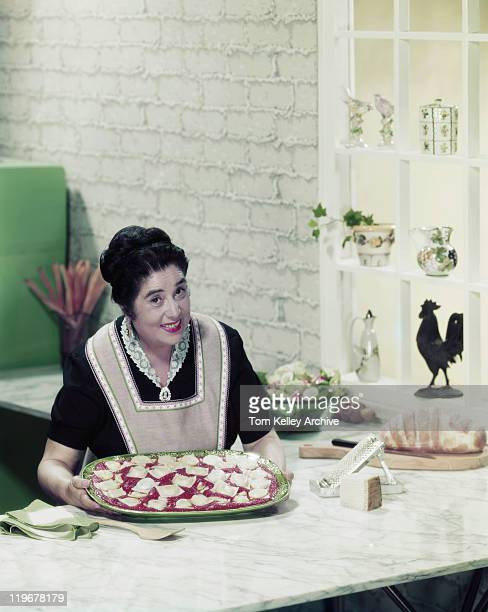mature woman holding tray of ravioli, smiling, portrait - 1957 stock pictures, royalty-free photos & images