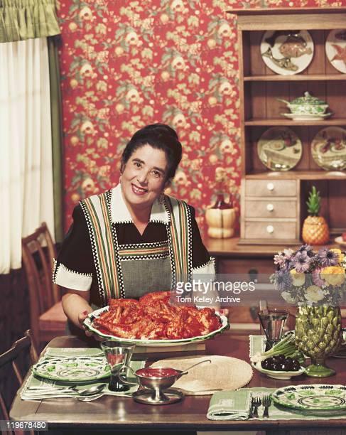 マチュア持つ女性のトレー鶏のロースト、笑顔、ポートレート