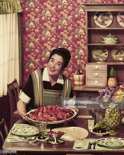 Mature woman holding tray of roasted chickens, smiling, portrait