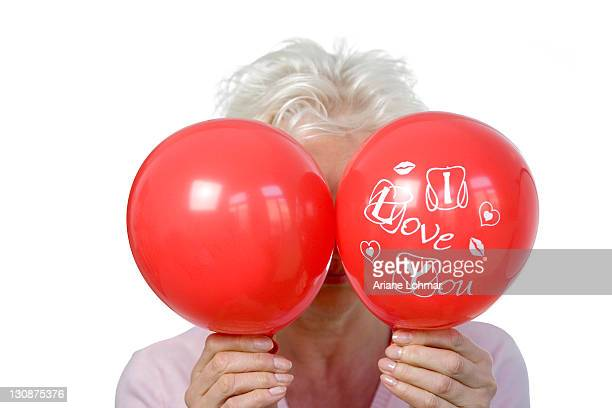 A mature woman holding two red balloons, saying I love you, in front of her face