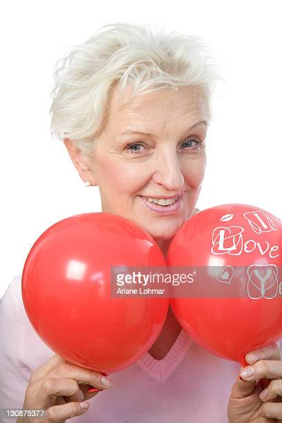 A mature woman holding two red balloons, saying I love you