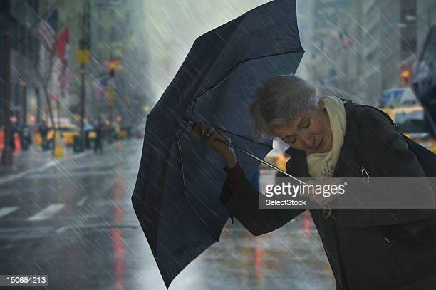 Mature woman holding umbrella against the wind
