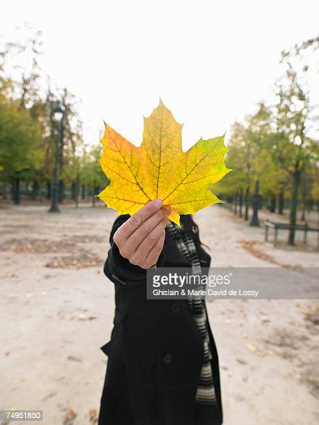 Mature woman holding up autumn leaf outdoors