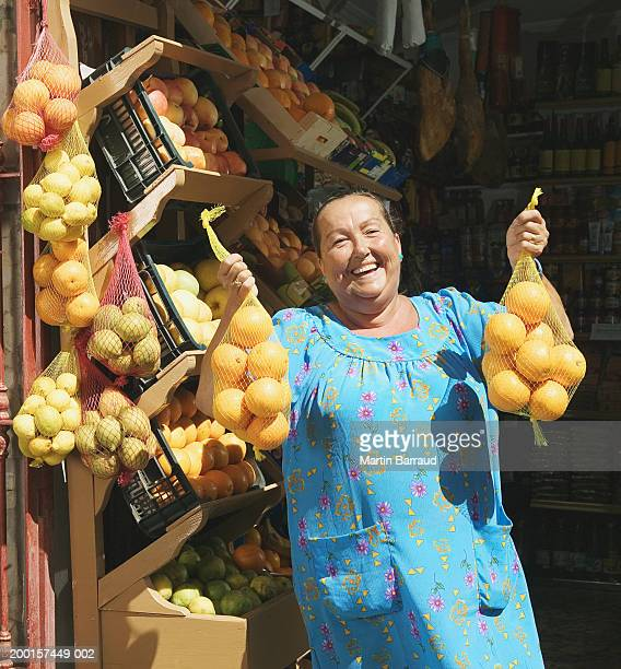 Mature woman holding up nets of oranges by fruit dispaly, portrait