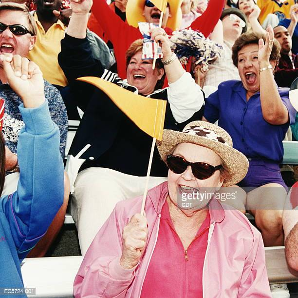 Mature woman holding yellow flag in stadium