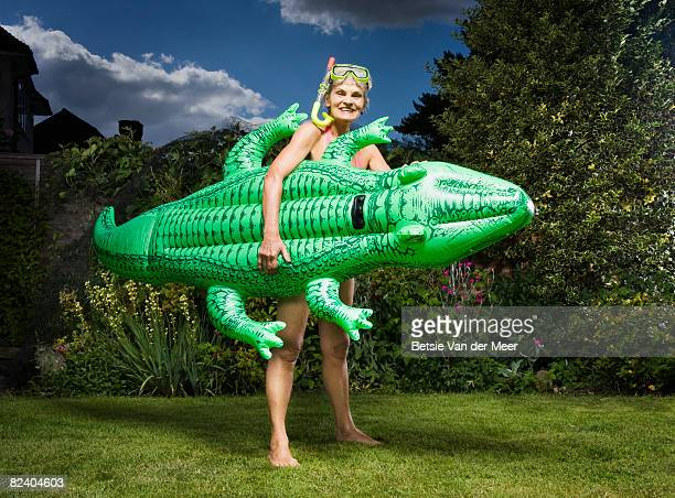 Mature woman holds inflatable crocodile in garden.