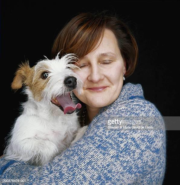 mature woman hugging dog - animaux domestiques photos et images de collection