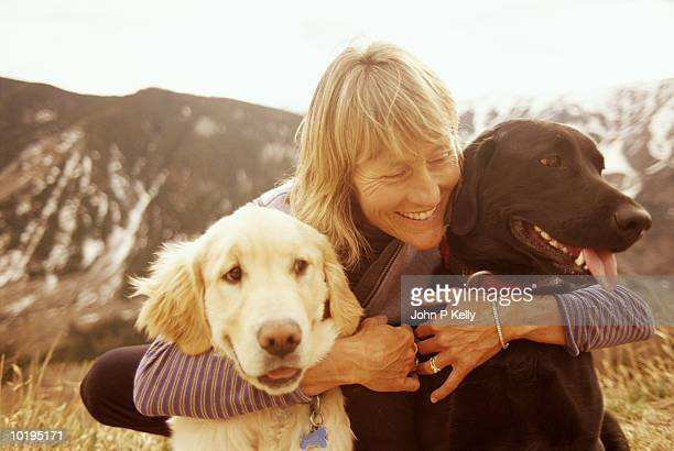 mature woman hugging dogs, aspen, colorado - 50 59 years stock pictures, royalty-free photos & images