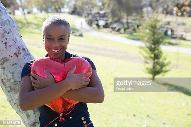 Mature woman hugging red heart-shaped balloon, Hahn Park, Los Angeles, California, USA