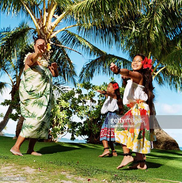 mature woman hula dancing with two girls (8-10), smiling - lei day hawaii stock pictures, royalty-free photos & images